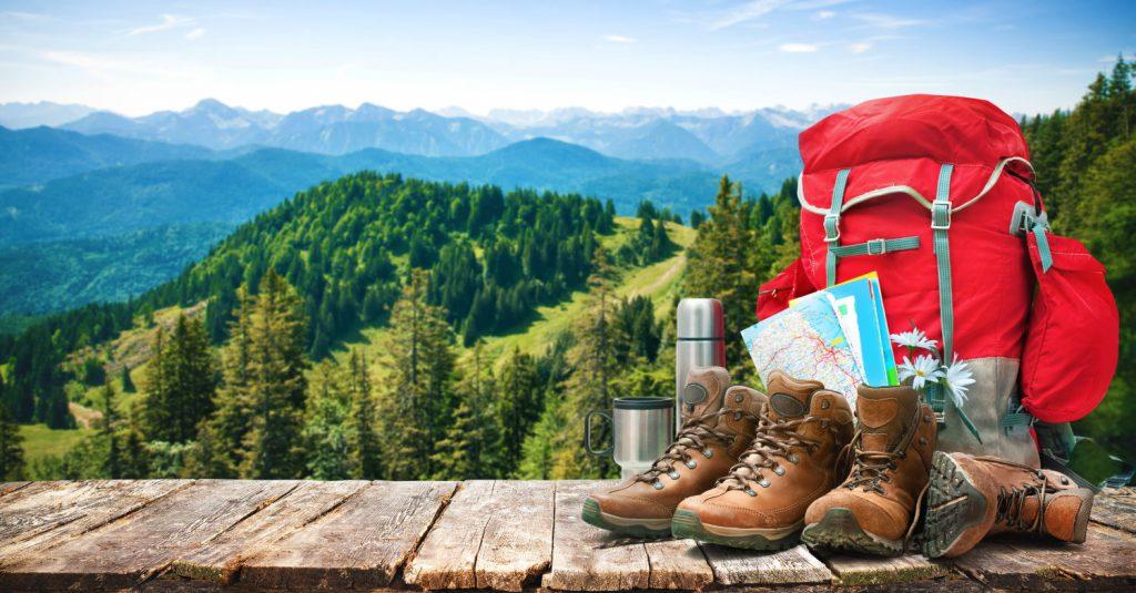 Wanderrucksack mit Wanderschuhe vor einem Bergpanorama. Wandern macht Spaß