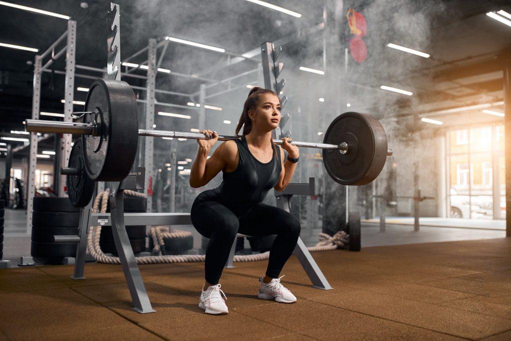 Frau beim Krsfttraing im Fitness. Kniebeuge mit Langhantel