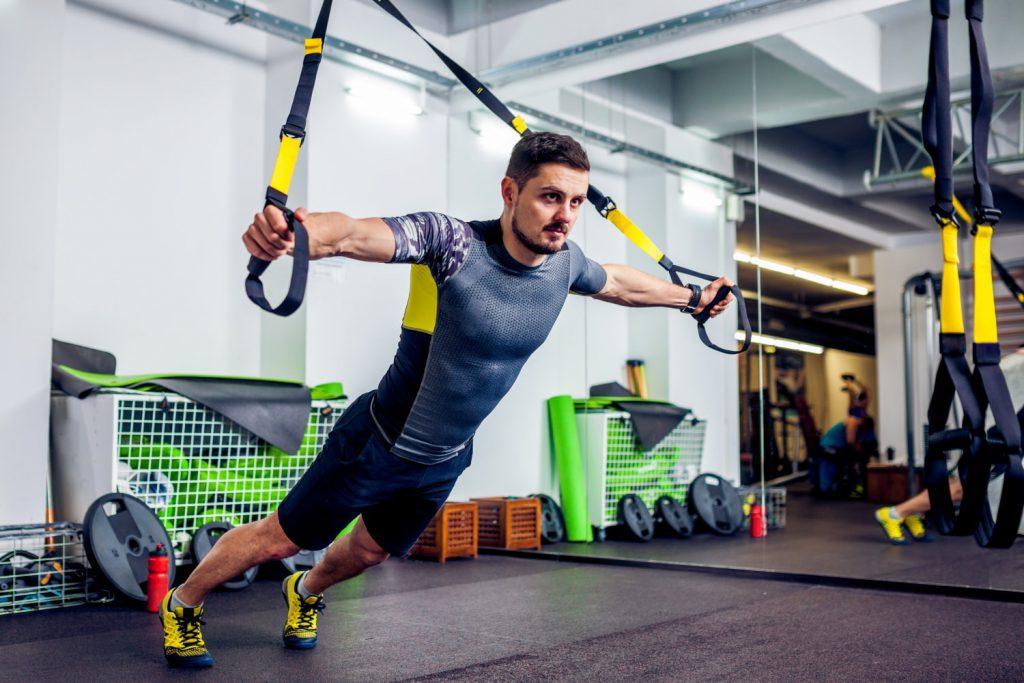 Mann beim Training mit einem Slingtrainer (TRX)