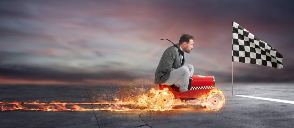 Mann auf einem kleinen Auto der auf die Ziellinie zufährt.