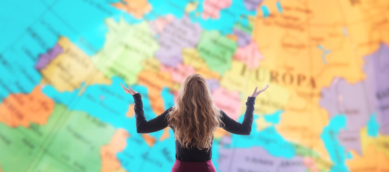 Frau vor einer Weltkarte bei der Reiseplanung.