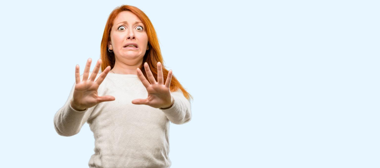 Frau hält ihre Hände in einer Abwehrhaltung. Verdeutlich das der anderen Person in Missgeschick passiert ist.