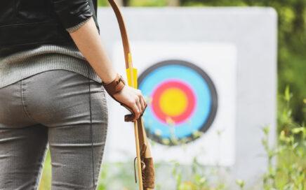 Bogenschützin mit Bogen vor einer Zielscheibe.