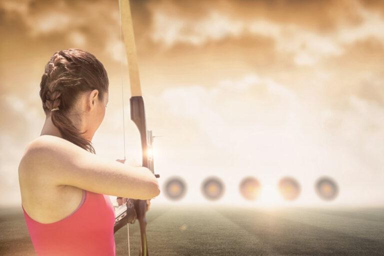 Frau beim Bogenschießen auf Zielscheiben