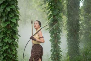 Langbogen mit asiatischer Bogenschützin im Wald