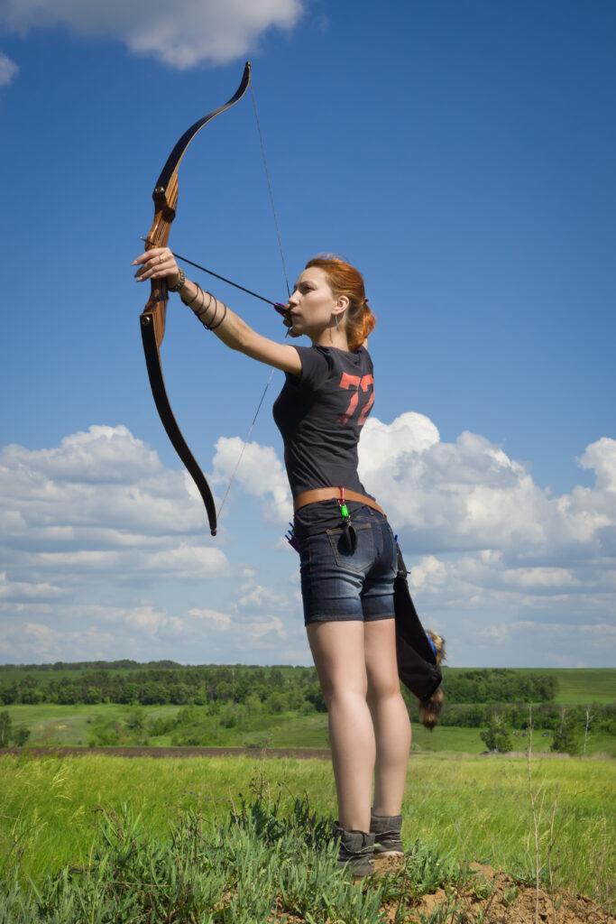 Bogenschützin mit Pfeil und Bogen auf dem Feld